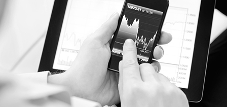 A man points at a graph of the stock market on his mobile device