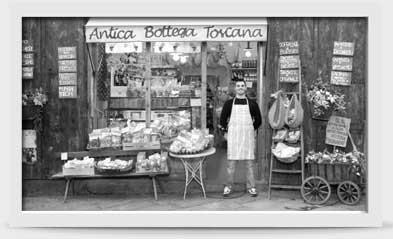 一名男性驕傲地站在其商店前的圖片