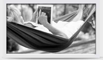 一位女士躺在吊床上使用平板電腦的圖片