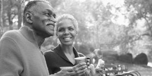 一對夫妻坐在公園內喝咖啡的圖片